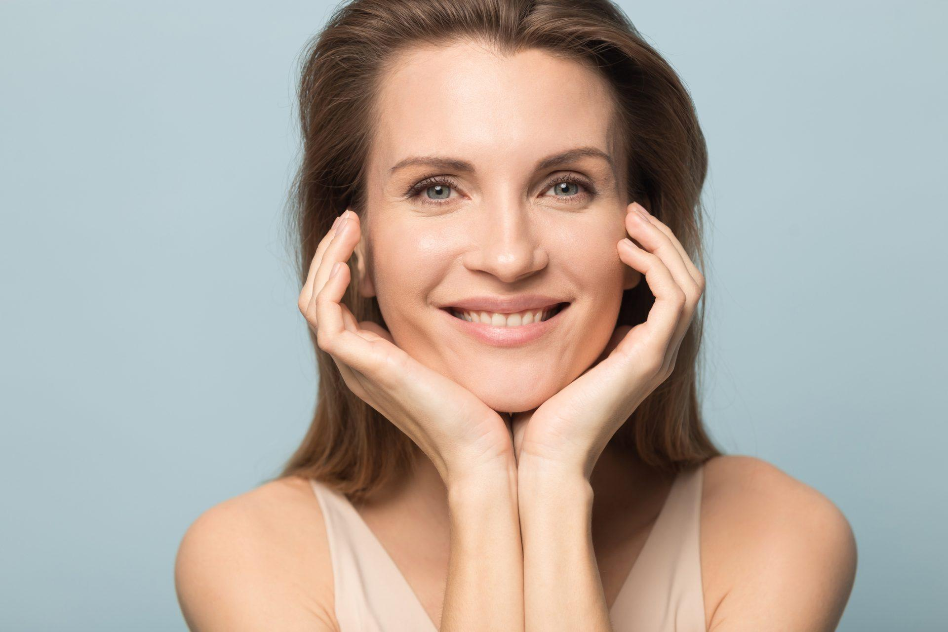 Close up portrait of happy beautiful Caucasian woman isolated on blue studio background look at camera demonstrate clean healthy skin, smiling millennial female show result after cream serum treatment